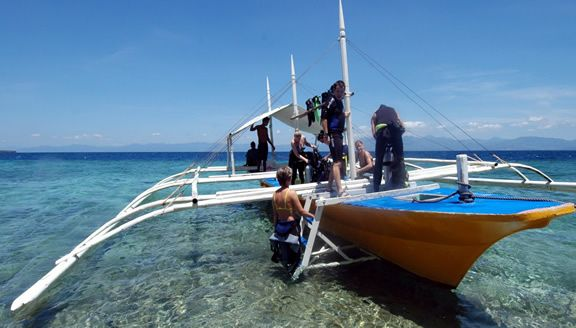 Scuba Divers boarding the dive boat heading out for a dive on nearby Pescador Island in Moalboal, Cebu