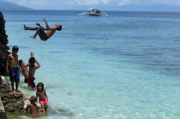 Kids frolicking at Panagsama Beach in Moalboal, Cebu